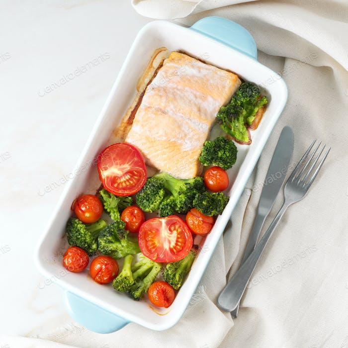 Fish salmon baked in oven with vegetables - broccoli, tomatoes. Healthy diet food, white marble