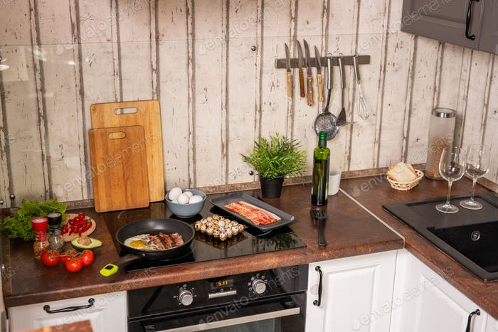 Part of contemporary kitchen with electric stove with frying bacon and eggs