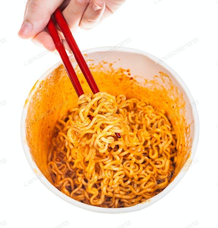 Hand hält rote Essstäbchen mit gekochten Nudeln