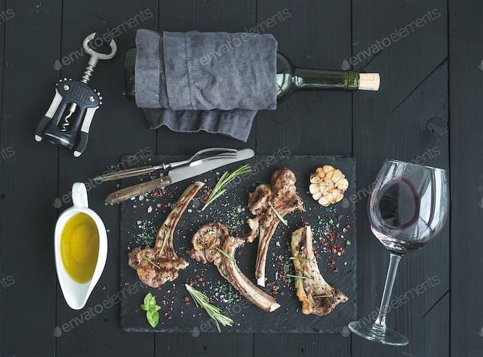 Lammregal mit Knoblauch, Rosmarin, Gewürze auf Schieferplatte, Weinglas, Öl in einer Untertasse