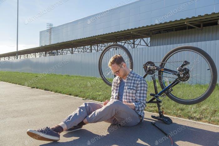 Upset man searches solution of a bicycle malfunction.