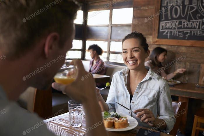 Over shoulder view of couple having lunch in a restaurant