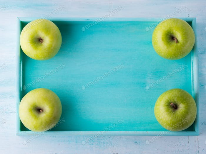 Green apples frame on turquoise tray
