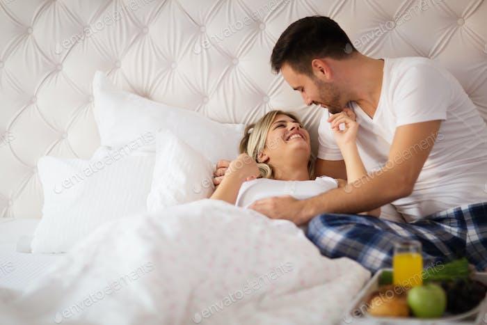 Romantic husband waking wife with breakfast