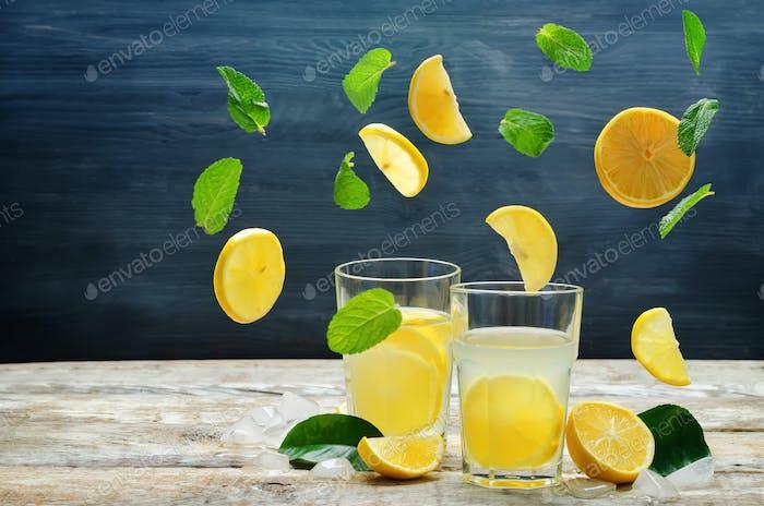 Lemonade with flying lemon, mint and ice