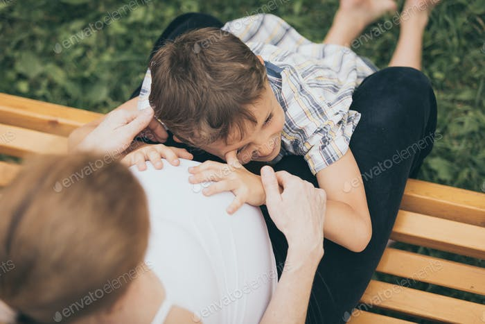 Happy little boy hugging mother in the park at the day time.