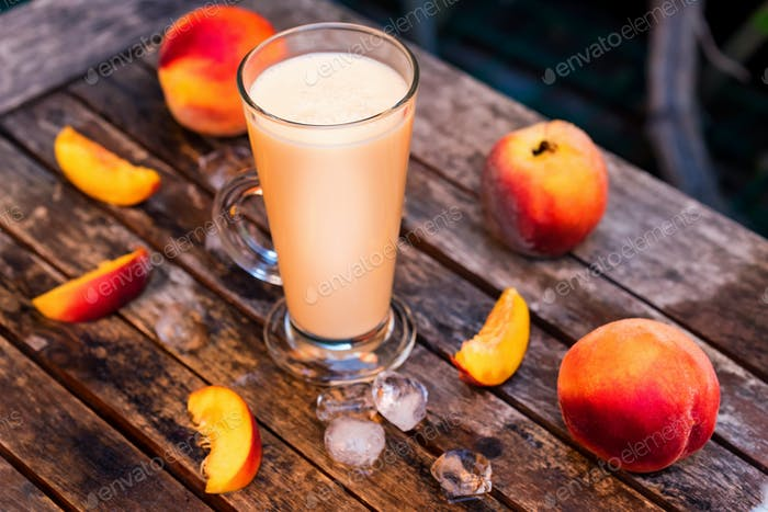 Glass of peach yoghurt and peaches on wooden table
