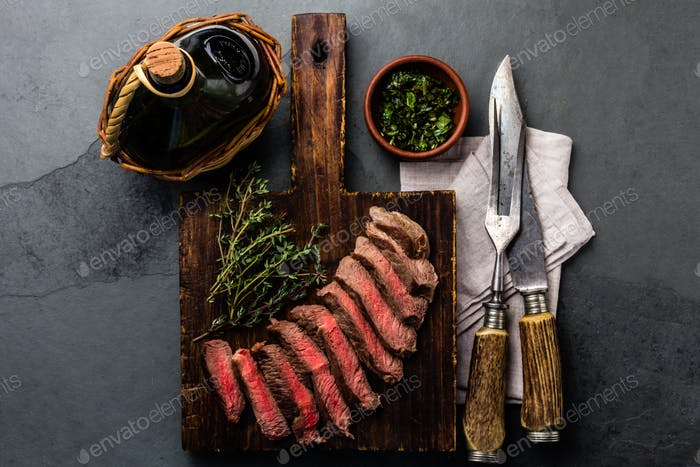Slices medium rare beef steak with herb sauce, bottle of wine, vintage cutlery, slate background