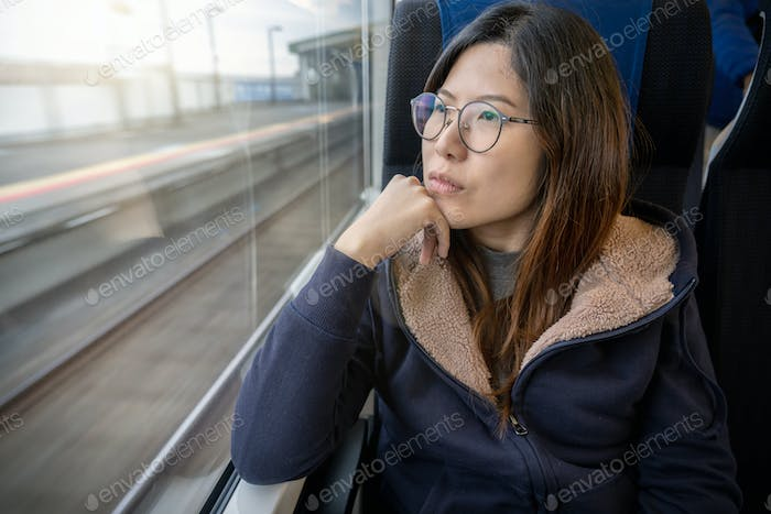 Asian Young lady passenger Sitting in a depressed mood beside the window inside Train