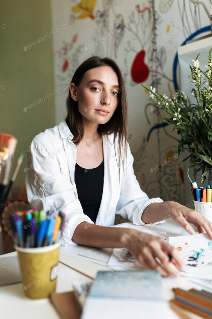 Young pensive painter sitting at the desk with pictures thoughtf