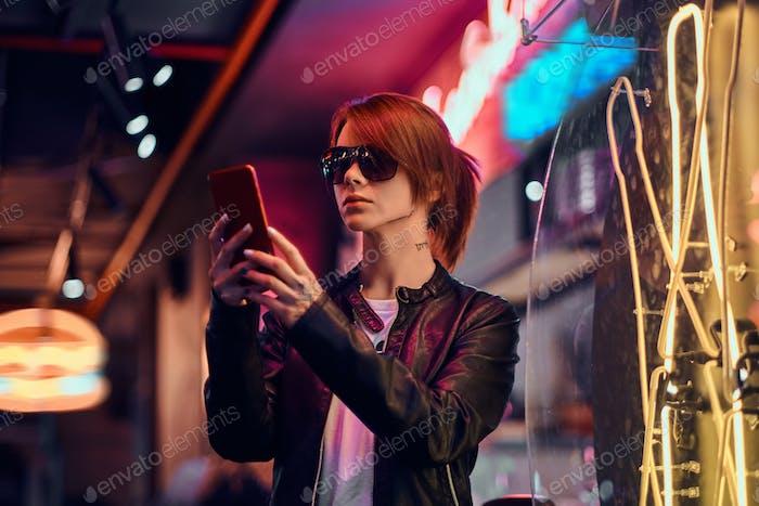 Стильная рыжая девушка пользуется телефоном, стоя ночью на улице.