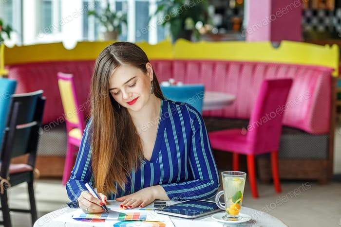 Young successful woman works at the table. The concept of work,