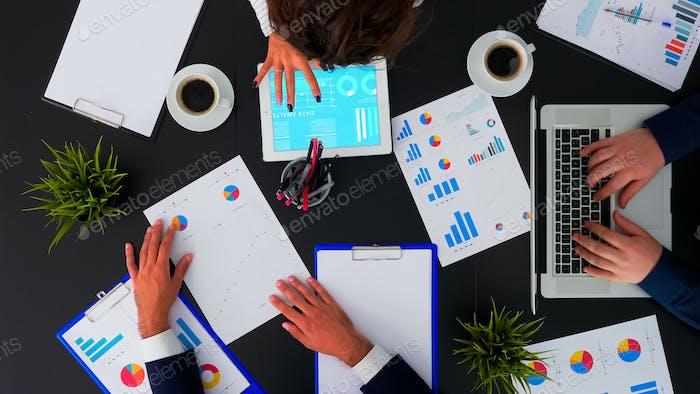 Empresarios que se reúnen analizando estadísticas financieras