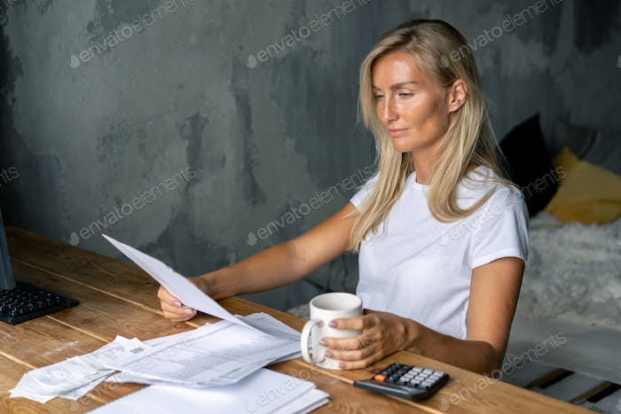 The woman at the table works with documents and bills