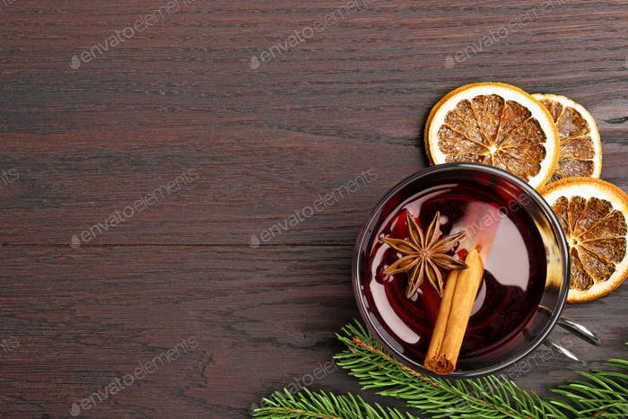 glass of mulled wine, orange and fir branch on wooden table