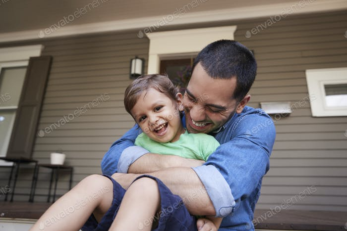 Father Hugging Son As They Sit On Porch Of House Together