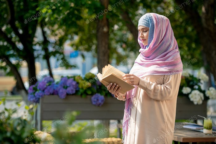 Casual young woman in hijab looking through book outdoors