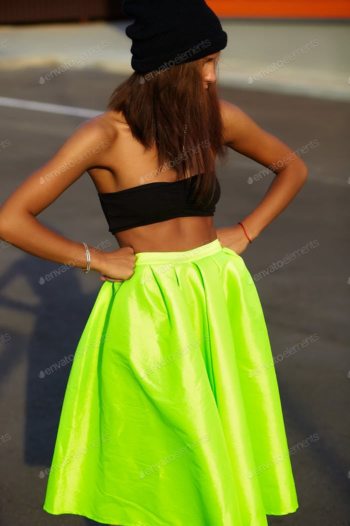 Woman in green skirt posing outdoors