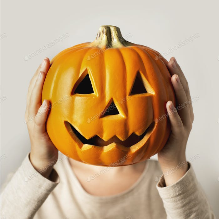 Close up of Woman with pumpkin face on gray