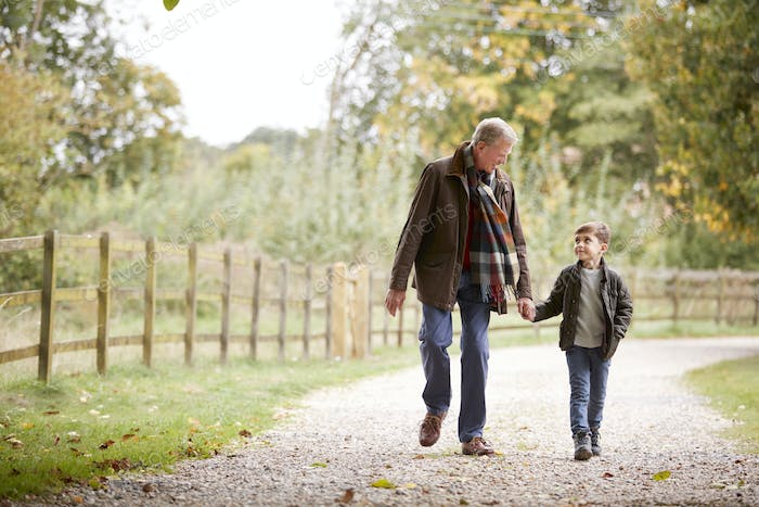 Grandfather With Grandson On Autumn Walk In Countryside Together
