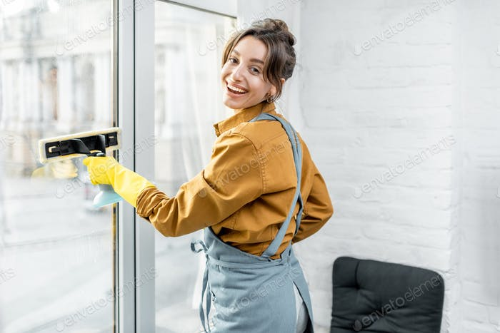 Housewife washing windows at home
