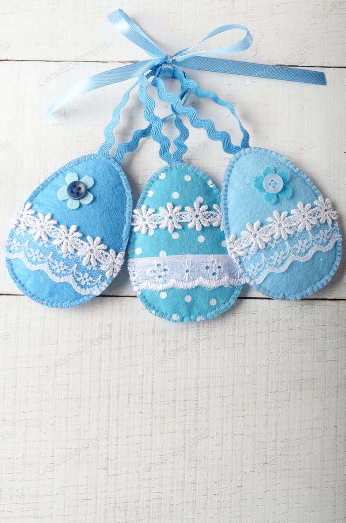 Handmade patchwork blue felt easter eggs on white wooden table