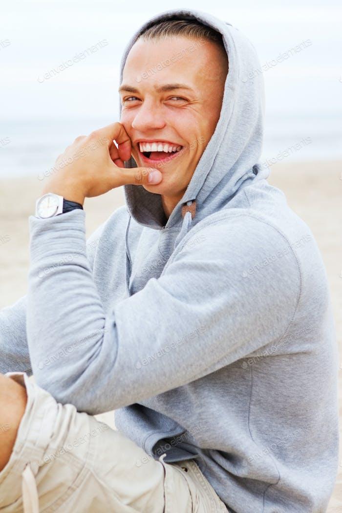 Portrait of man sittin on the beach in a coat