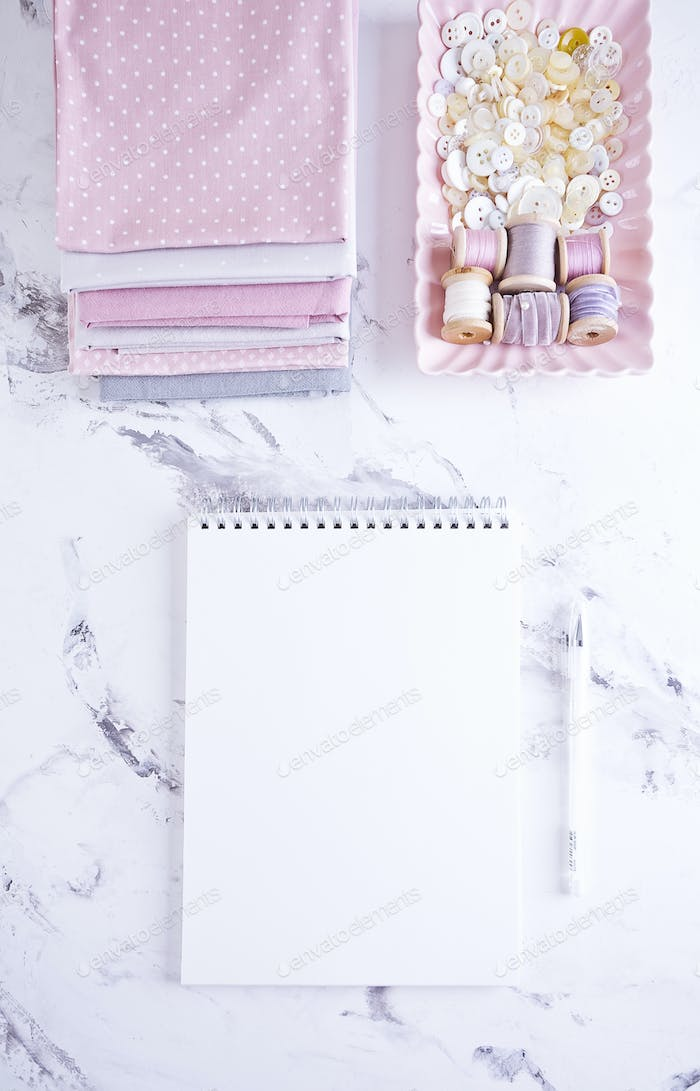 White Empty Notebook with sewing items over marble table