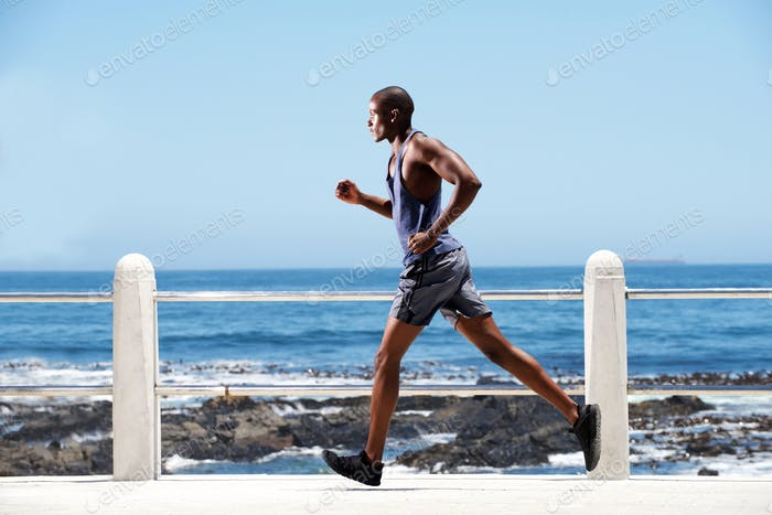 Full length fit young african american man running by the sea