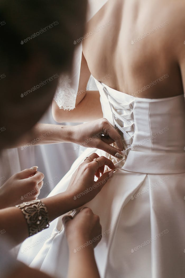 bridesmaids and mother helping gorgeous bride getting ready for wedding