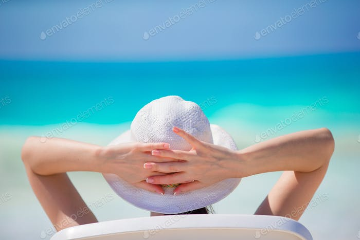 Young woman in hat on a tropical beach