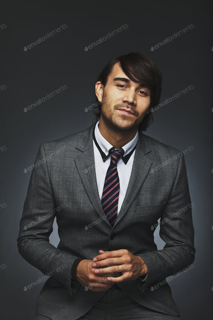 Confident young businessman against black background