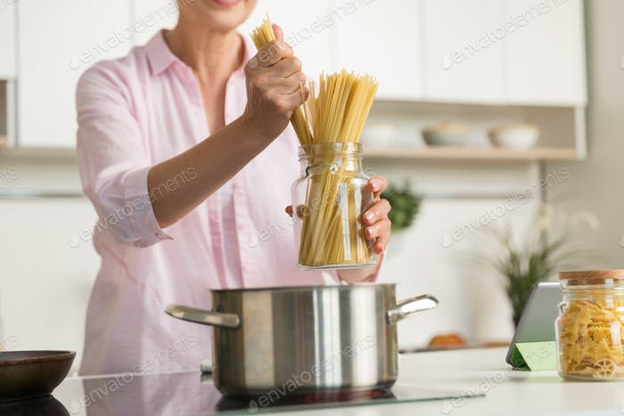 Cropped picture of mature woman cooking.