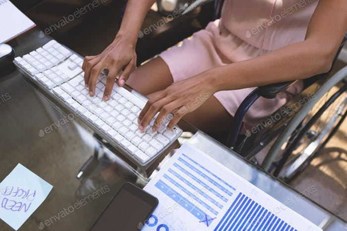 Mid-section of young disabled mixed-race businesswoman working on computer at desk in the office