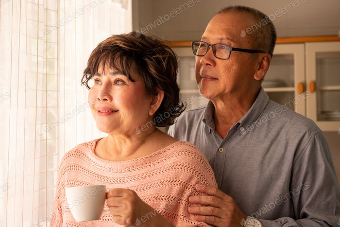 Happy asian couples standing together and looking outside.
