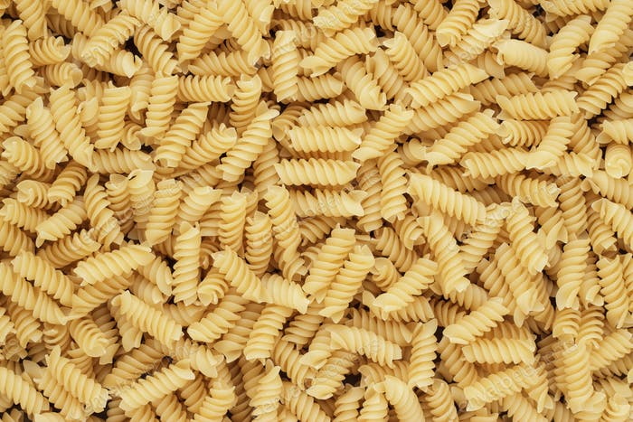 dry uncooked rotini texture background