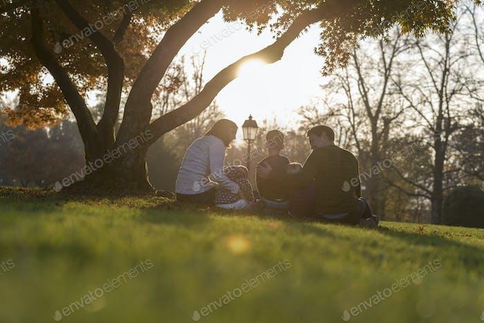 Junge Familie mit drei Kindern sitzen unter Herbstbaum