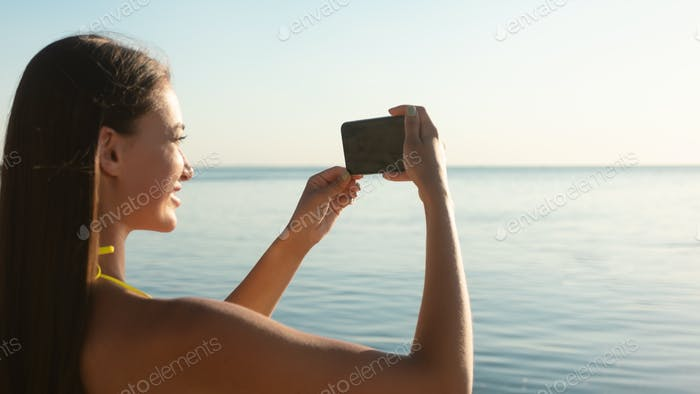 Girl With Smartphone Taking Pictures Of Sea Outdoors, Wearing Swimwear