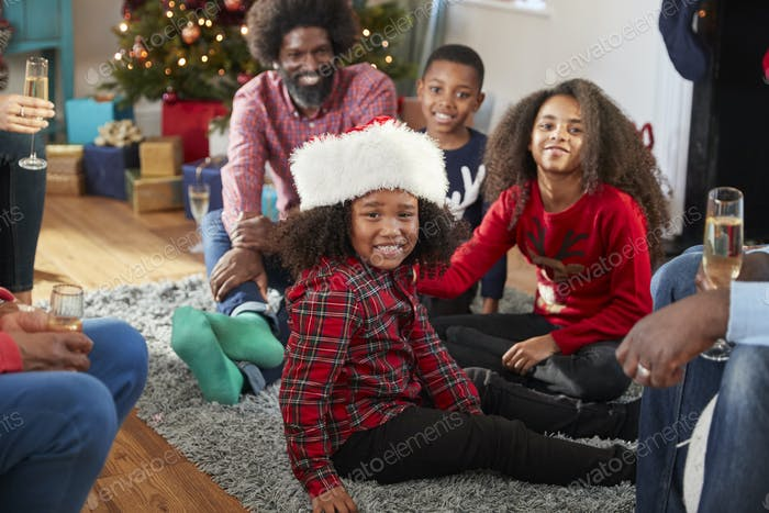 Portrait Of Boy Wearing Santa Hat As Multi Generation Family Celebrate Christmas At Home Together