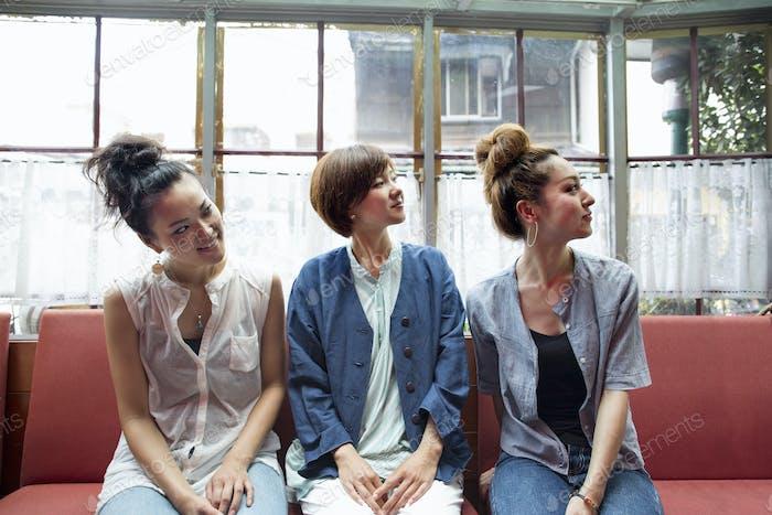 Tres mujeres sentadas en un banco, mirando hacia otro lado.