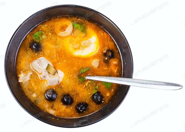 top view of Solyanka fish soup in bowl with spoon