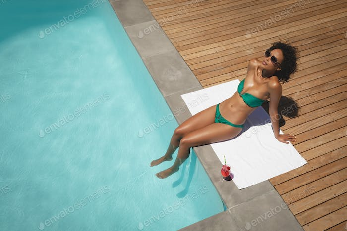 Beautiful young woman sitting at poolside in her backyard on a sunny day