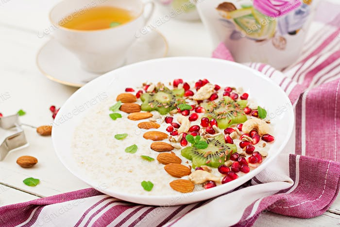 Tasty and healthy oatmeal porridge with kiwi, pomegranate and seeds.