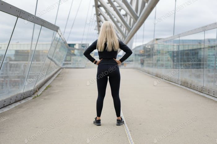 Back of fit blonde woman runner standing on bridge in modern looking city