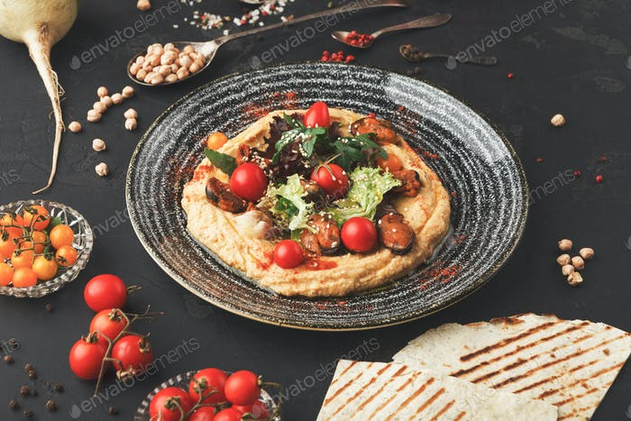 Hummus with vegetables and seafood on black background