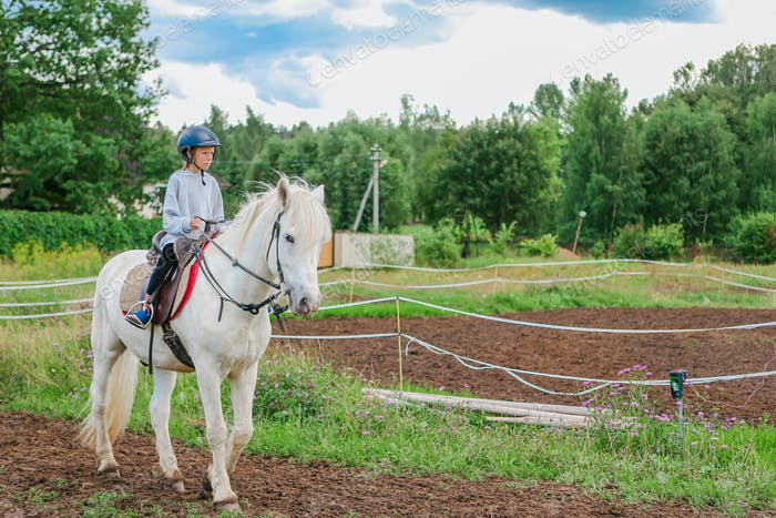 Girl riding a white horse on nature