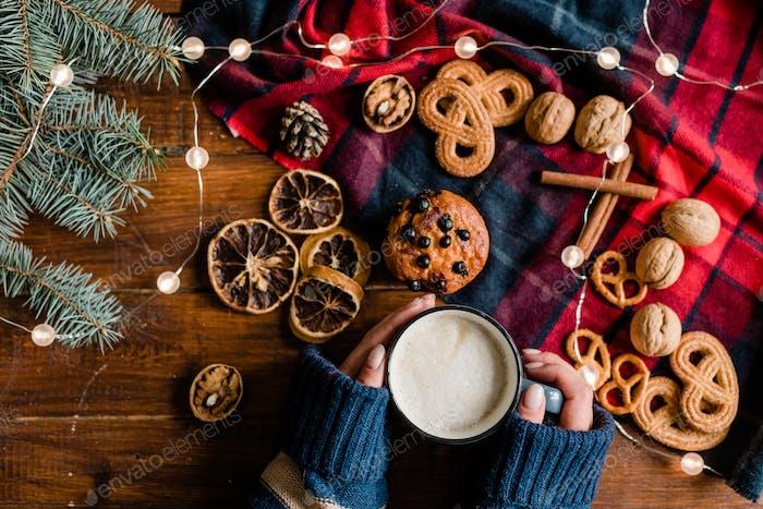 Mädchen halten Tasse mit Heißgetränk umgeben von traditionellen Weihnachtsessen und Symbolen