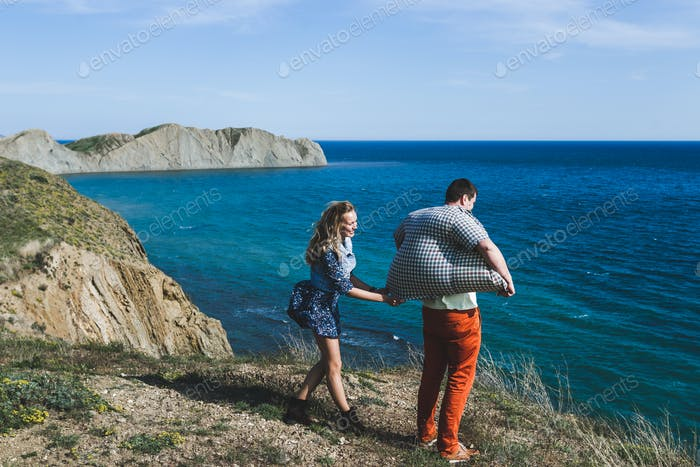 Funny photo of young couple. Shirt inflated by the wind from the sea.