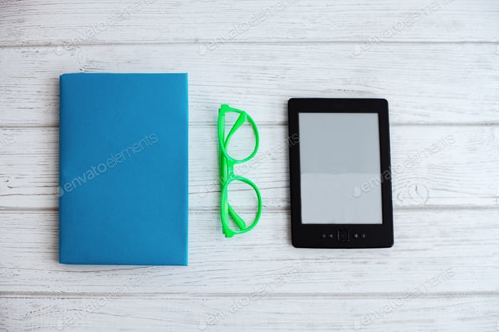 Printed books and e-book on a white background and glasses. The