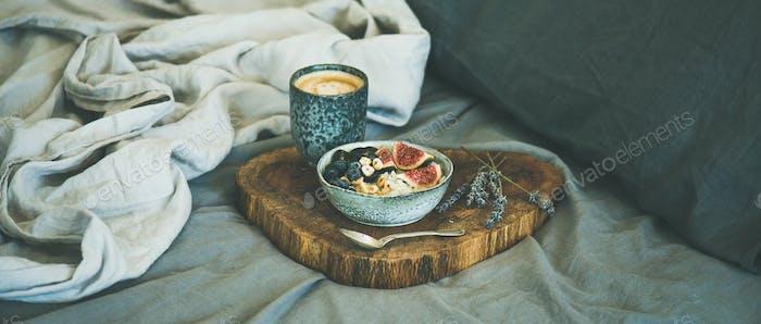 Rice coconut porridge and espresso in bed, wide composition